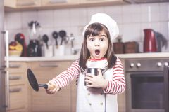 Cute little girl in the kitchen. Surprised little girl chef having a funny reaction Stock Photo