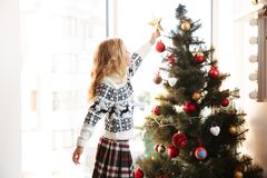 Cute little girl in knitted sweater placing star on the top of C Stock Image