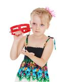 Cute little girl knocks on the tambourine Stock Photo