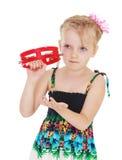 Cute little girl knocks on the tambourine Stock Photo