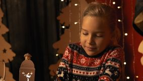 Cute little girl with a lantern writes a letter to Santa Claus on Christmas Eve in slow motion stock video footage