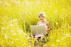 Cute little girl with laptop on nature Royalty Free Stock Images