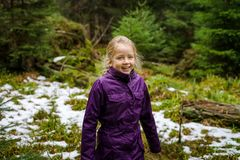 Cute little girl laughing, autumnal forest with first snow, France royalty free stock photo