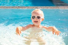 Cute little girl laughing and having fun splashing in the pool. stock image