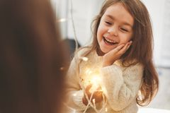 Cute little girl laughing and looking at morror with bright christmas garland in her hands. Christmas portrait, cozy style. Close up portrait royalty free stock photo