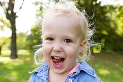 Cute little girl laughing outdoors. Close up portrait of a cute little girl laughing outdoors royalty free stock photo