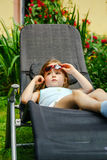 Cute little girl laying in the chaise lounge. Small garden royalty free stock photo