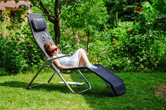Cute little girl laying in the chaise lounge. Small garden royalty free stock images