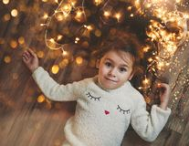 Cute little girl laying on flor with bright christmas garland in her hair. Christmas portrait, cozy style. Top view stock photography