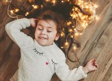 Cute little girl laying on flor with bright christmas garland in her hair. Christmas portrait, cozy style. Top view royalty free stock photo