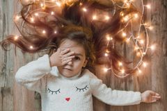 Cute little girl laying on flor with bright christmas garland in her hair. Christmas portrait, cozy style. Top view stock images