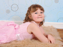 Cute little girl laying on a furry brown rug Royalty Free Stock Image
