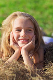 Cute little girl laying in hay heap. Cute little girl with blond hair laying in hay heap on green lawn Royalty Free Stock Photo