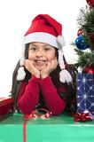 Cute Little Girl leaning on Presents smiling next to Xmas Tree Stock Photography
