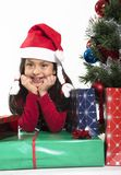 Cute Little Girl leaning on Presents smiling next to Xmas Tree Stock Photos