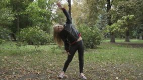 Cute little girl leans to the sides in slowmotion and has fun in park stock video footage