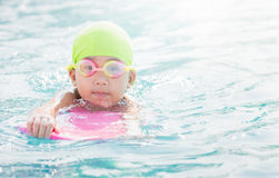 Cute little girl learning how to swim. stock image