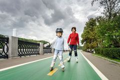 Cute little girl learning rollerskating with her mother Stock Photography