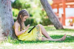 Cute little girl learning with tablet pc Royalty Free Stock Images