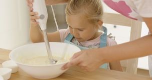 Cute little girl learning to bake from mother Royalty Free Stock Image