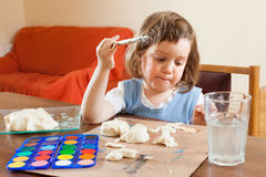 Cute little girl learning to paint dough figurines Stock Photography