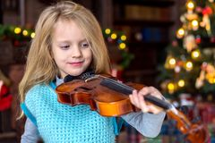 Cute little girl learning to play violin royalty free stock photography