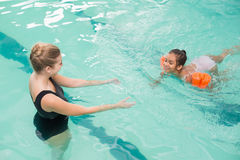 Cute little girl learning to swim with coach Stock Image