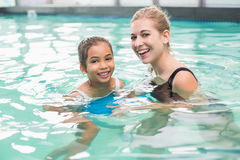 Cute little girl learning to swim with coach. At the leisure center Stock Photo