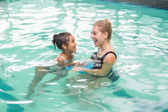 Cute little girl learning to swim with coach. At the leisure center Stock Image