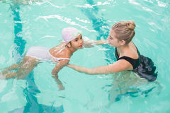 Cute little girl learning to swim with coach Stock Photography