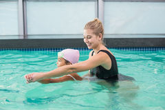 Cute little girl learning to swim with coach. At the leisure center Royalty Free Stock Photos