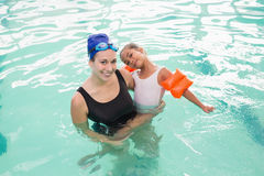 Cute little girl learning to swim with coach Royalty Free Stock Photo