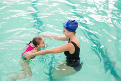 Cute little girl learning to swim with coach. At the leisure center Royalty Free Stock Image