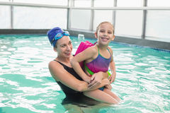Cute little girl learning to swim with coach. At the leisure center Royalty Free Stock Images