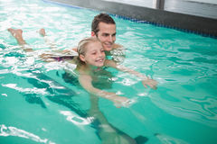 Cute little girl learning to swim with coach Royalty Free Stock Photos