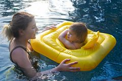 Cute little girl learning to swim with mother in pool. In sunset royalty free stock photos