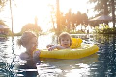 Cute little girl learning to swim with mother in pool. In sunset royalty free stock images