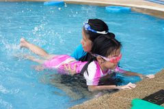 Cute little girl learning to swim with mother in swimming pool.  royalty free stock photos