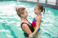 Cute little girl learning to swim with mum. At the leisure center Stock Photos