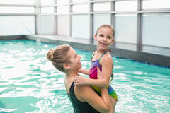 Cute little girl learning to swim with mum. At the leisure center Royalty Free Stock Photos