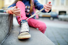 Cute little girl learning to tie shoelaces outdoors Stock Images