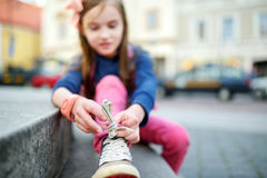 Cute little girl learning to tie shoelaces outdoors Royalty Free Stock Photos