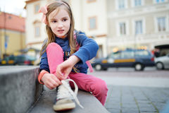 Cute little girl learning to tie shoelaces outdoors Royalty Free Stock Image