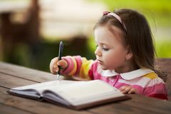 Cute little girl learning to write. Outdoors Stock Photography