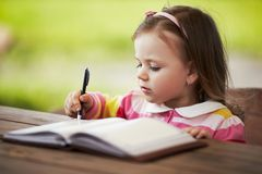 Cute little girl learning to write. Outdoors Royalty Free Stock Photo