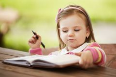 Cute little girl learning to write. Outdoors Royalty Free Stock Image