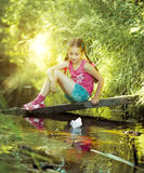 Cute little girl let a paper boat Stock Images