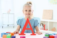 Cute little girl with letter A and colorful cubes. At home Royalty Free Stock Image
