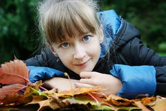 Cute little girl lie on the autumn leaves Stock Photography