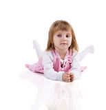 Cute little girl lie on the floor. Cute little girl in a pink lie on the floor. Studio shot stock photo